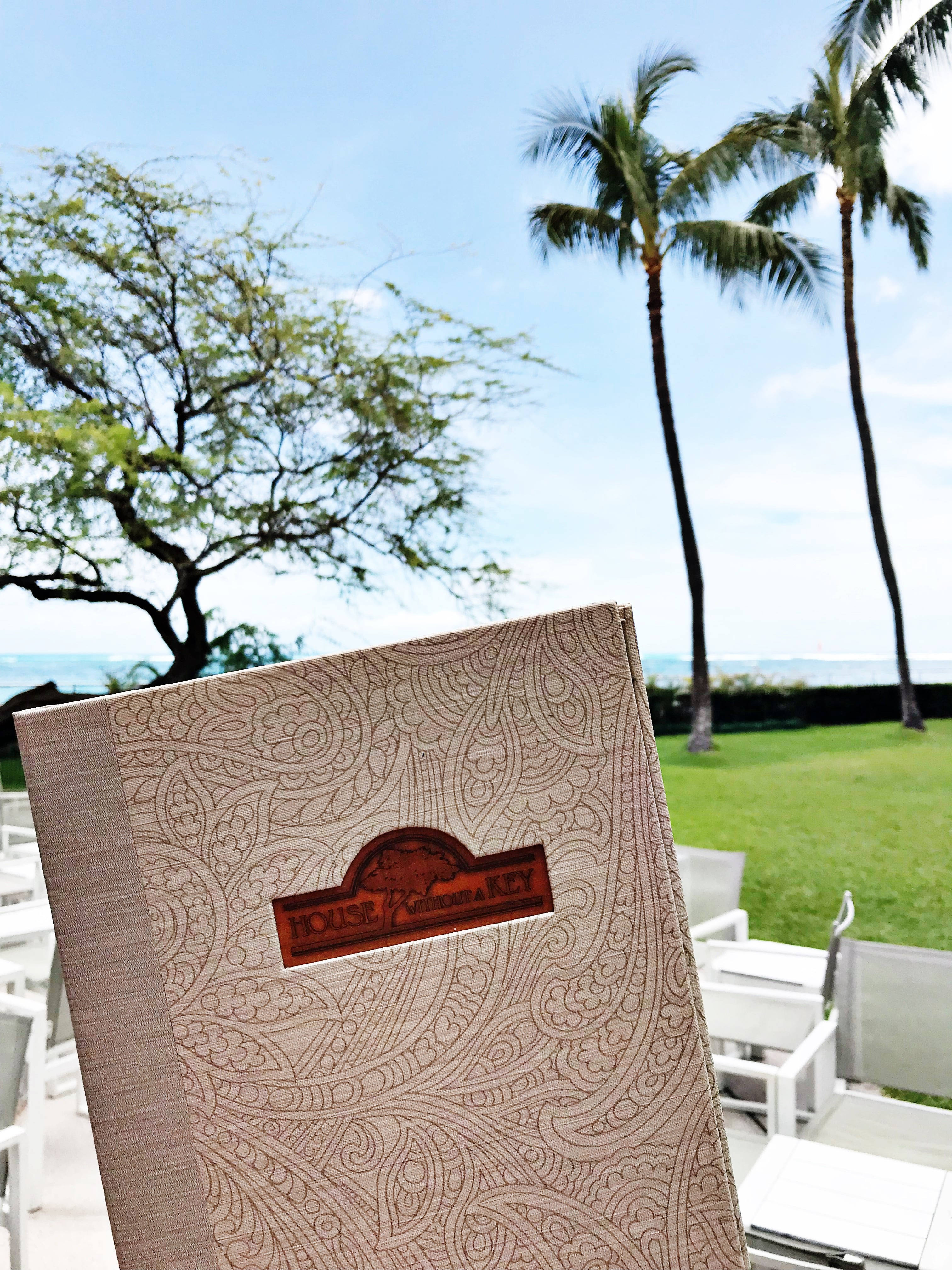 House Without A Key restaurant menu at Halekulani Hotel in Waikiki, holding up menu with palm trees in the background