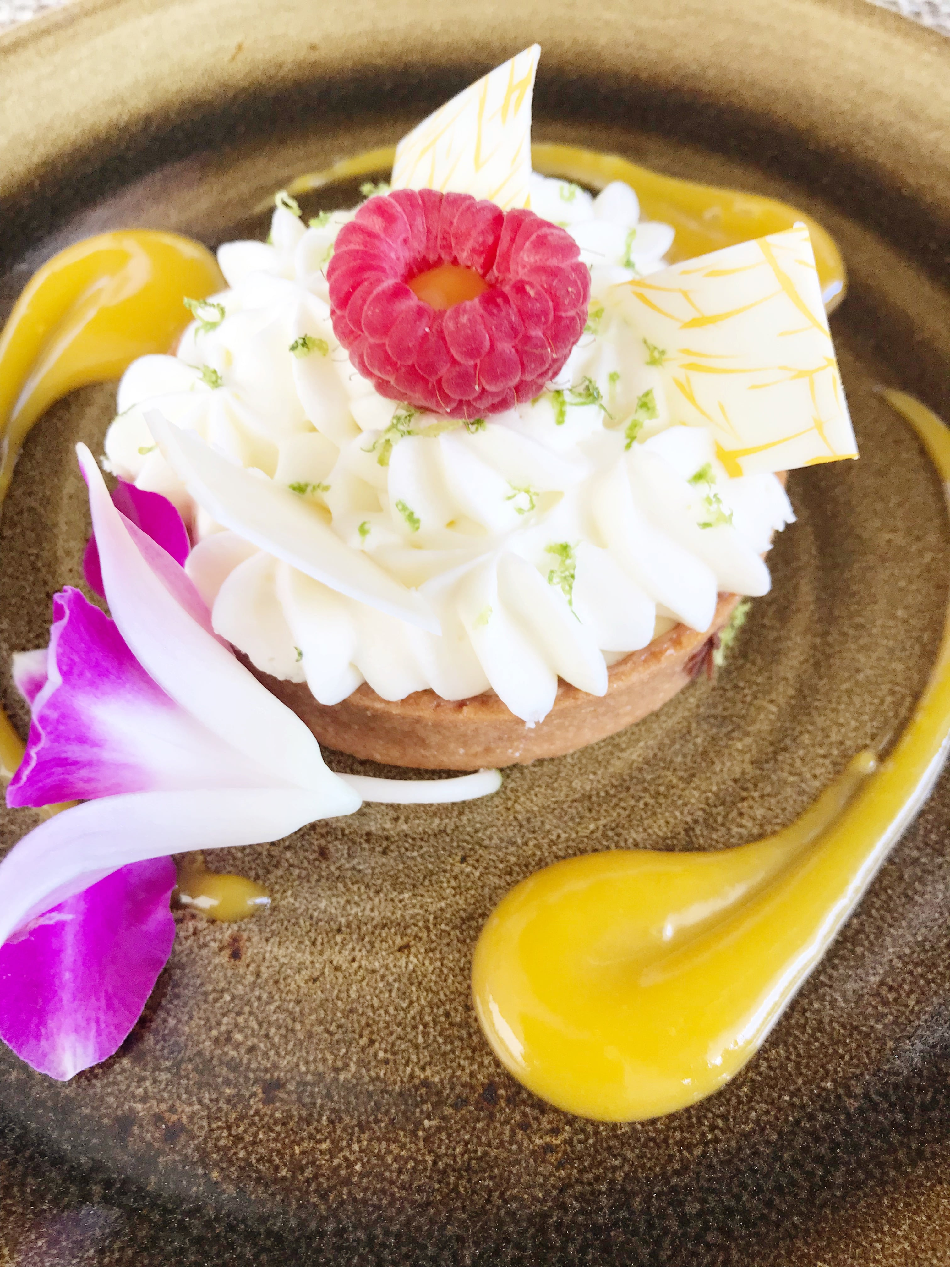 Eating At Halekulani's Restaurant House Without A Key, Key Lime Pie tartlette on a plate with a pink flower