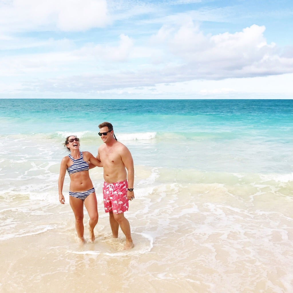 Couple standing on a beach in swimwear.