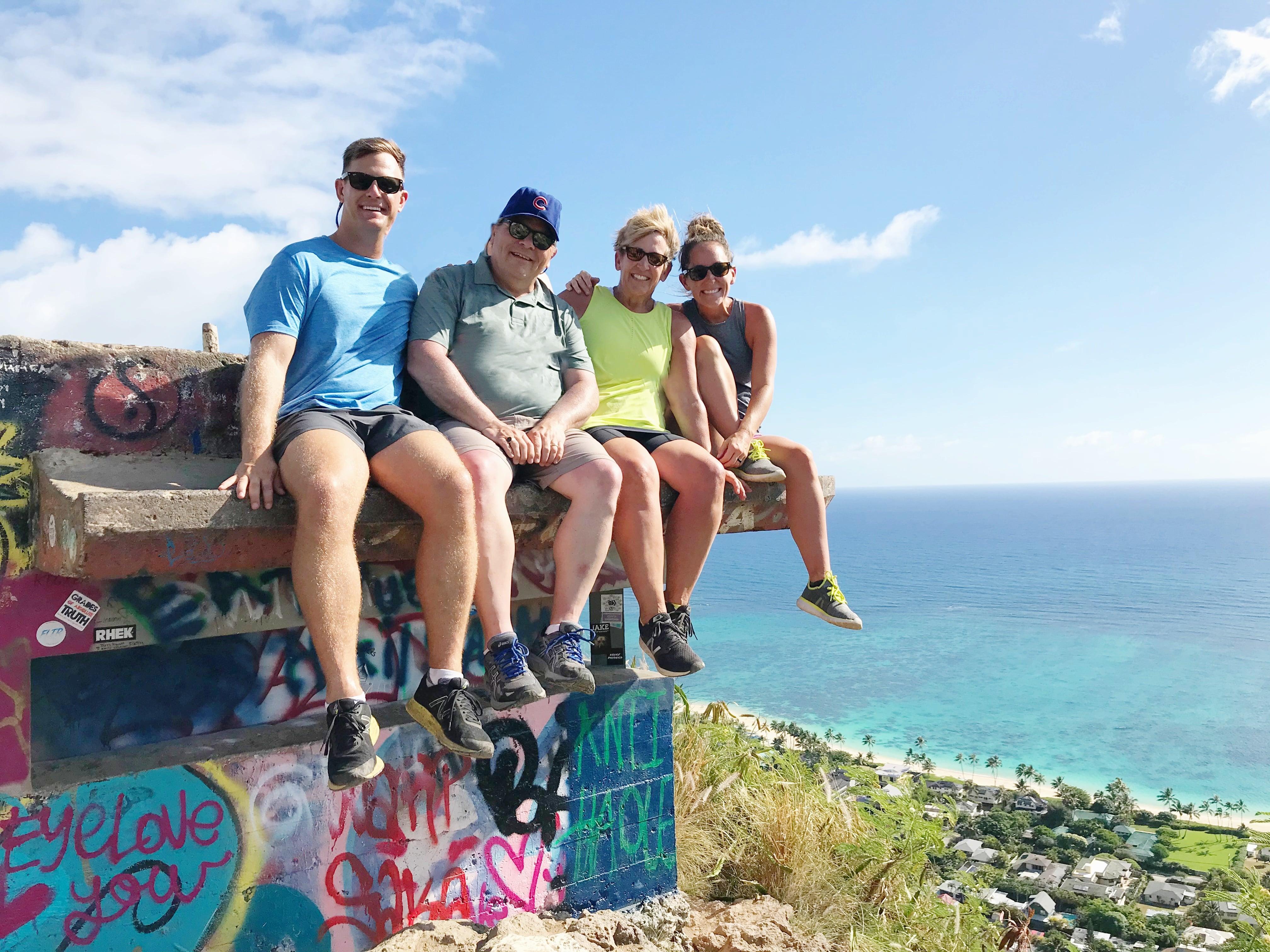 4 adults sitting on Lanikai Pillbox in Hawaii