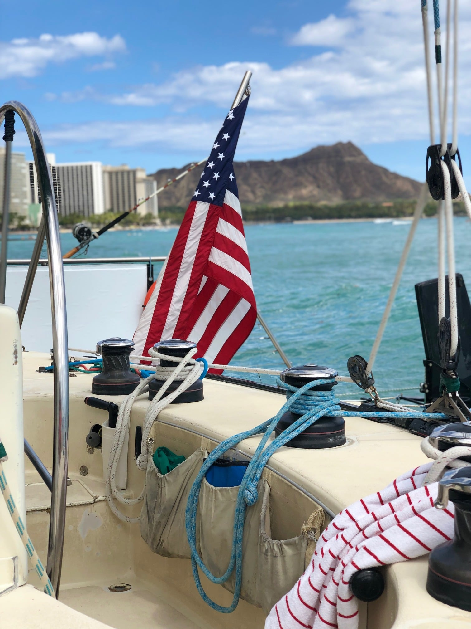 American flag on the back of a boat with Diamond Head Crater in the background.