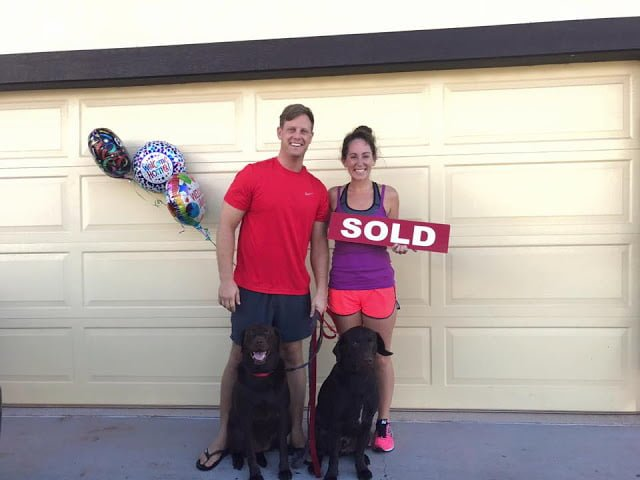 Couple and two dogs with SOLD sign