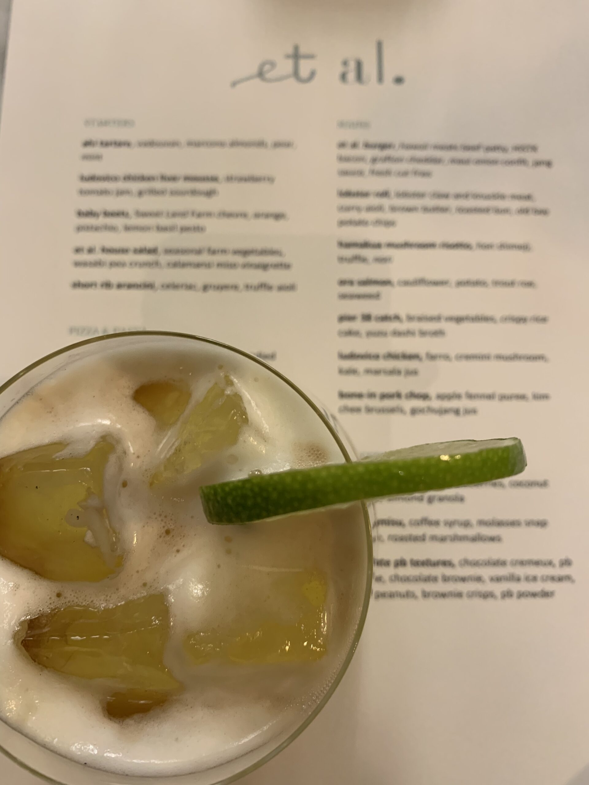 Cocktail garnished with a lime wedge sitting on a menu