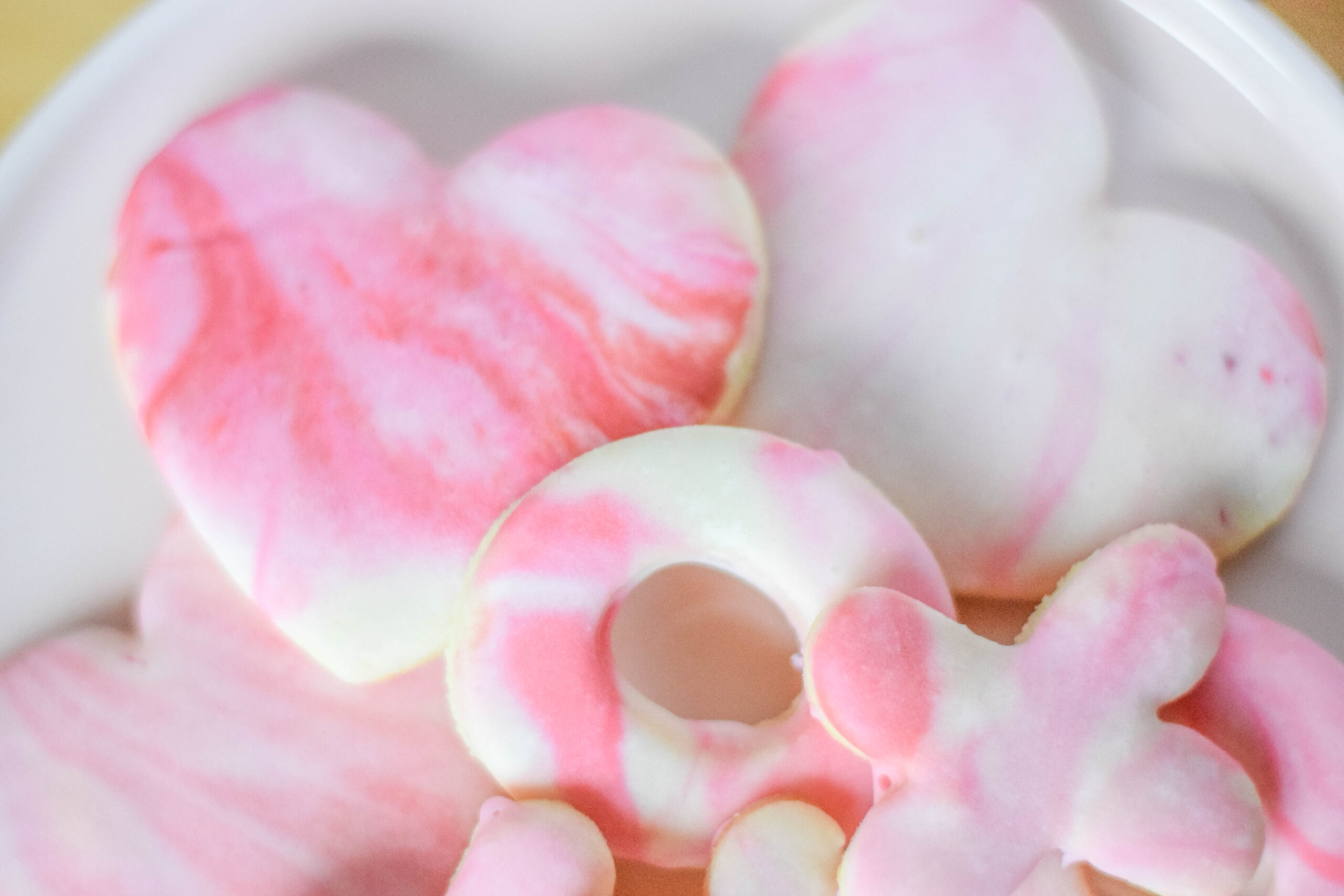 XOXO and heart-shaped sugar cookies with red, pink, and white marble icing