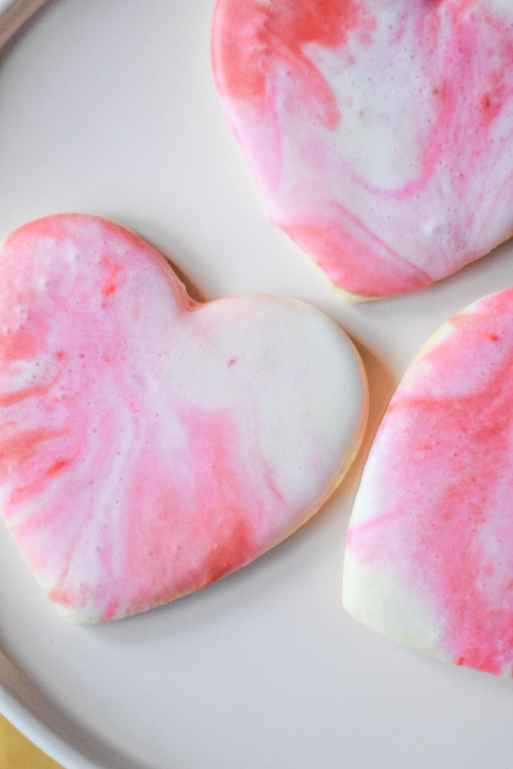 Heart shaped sugar cookies with pink, red, and white icing