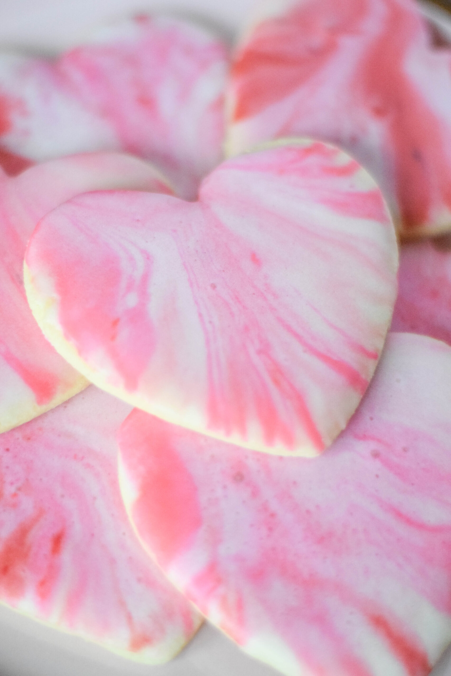 Stack of heart-shaped sugar cookies with red, pink, and white marble icing