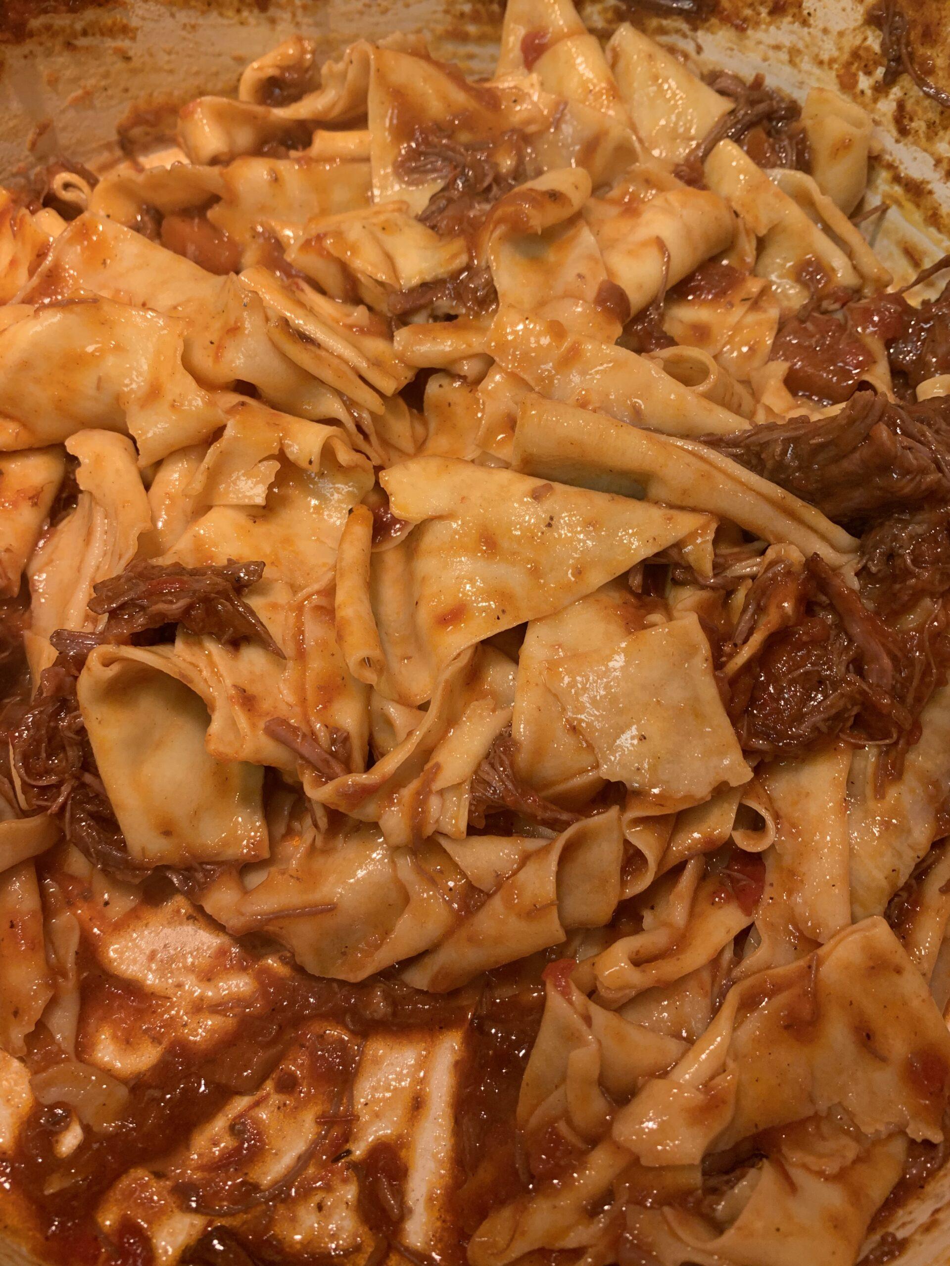 Papardelle pasta noodles mixed with short rib ragu sauce