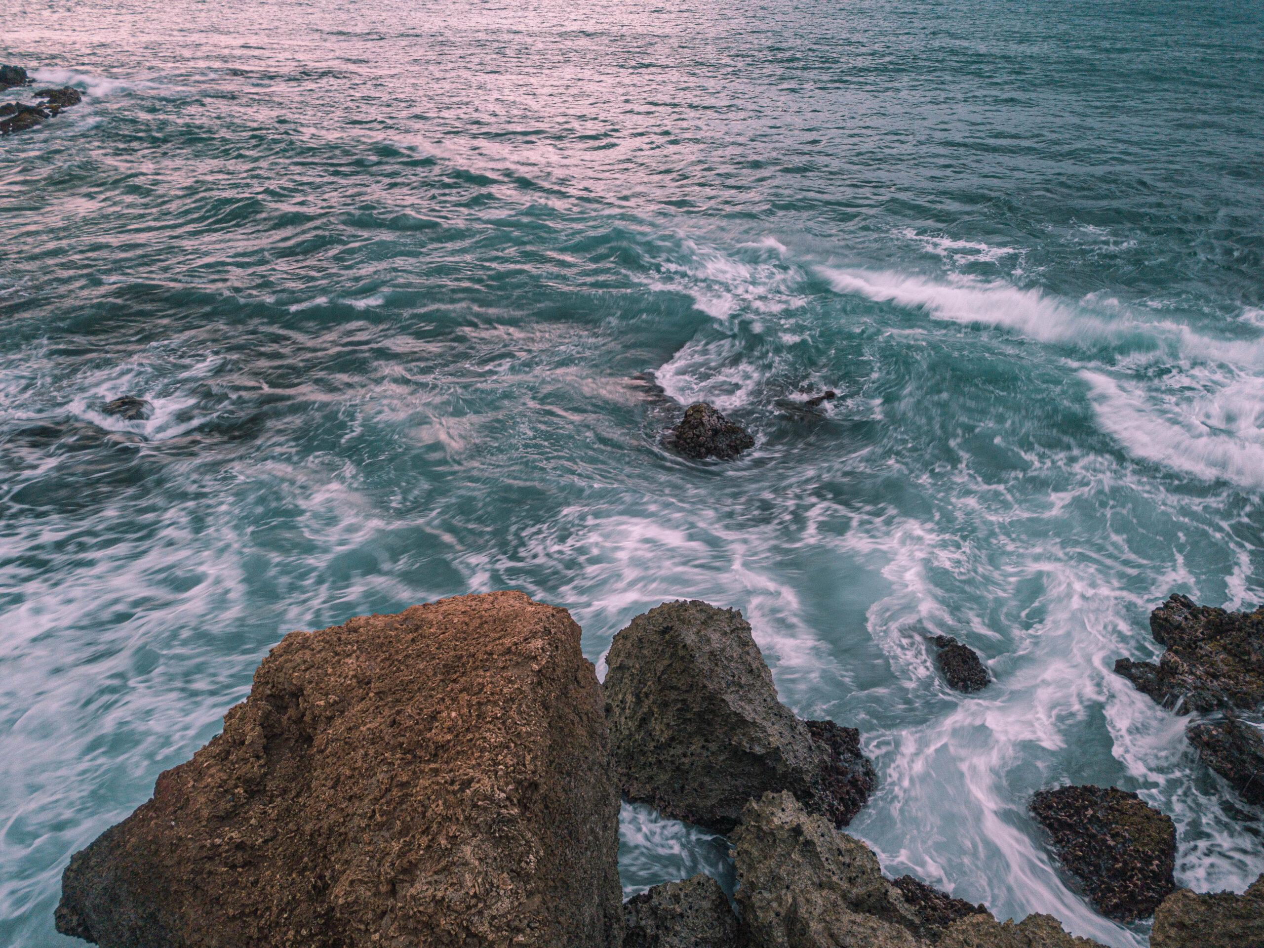 Ocean water swirling around rocks at sunset
